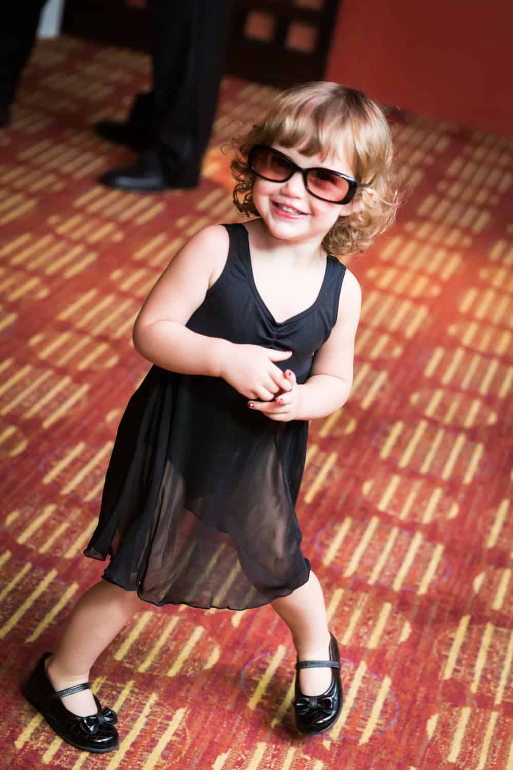 Little girl in black dress and sunglasses dancing