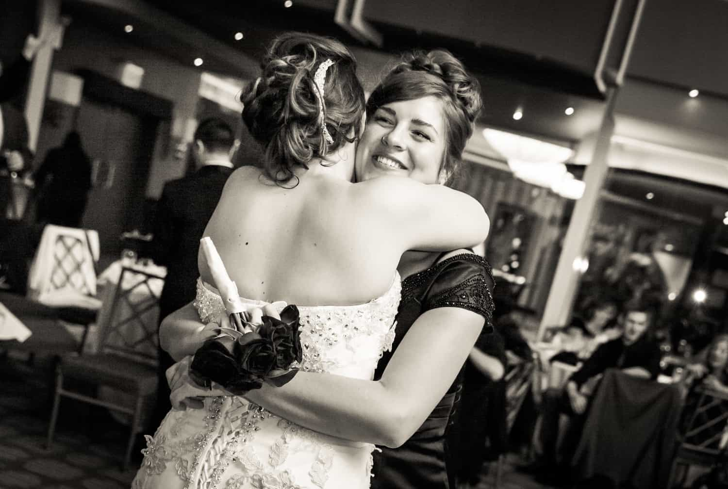 Black and white photo of bridesmaid hugging bride with bouquet