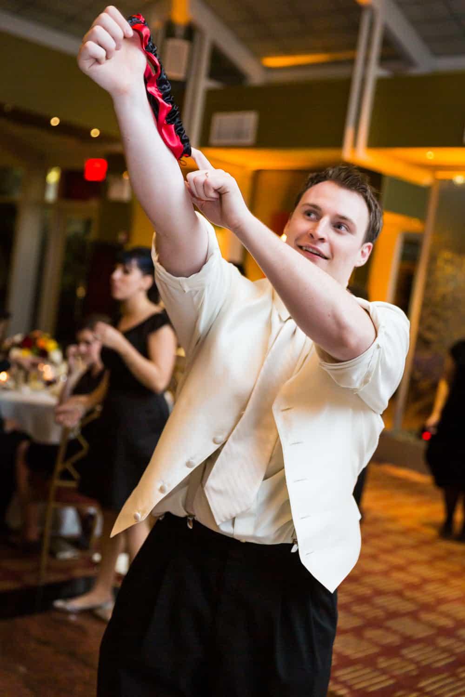 Nicotra's Ballroom wedding photos of groom launching garter belt in air