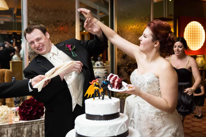 Nicotra's Ballroom wedding photos of bride trying to put cake on groom