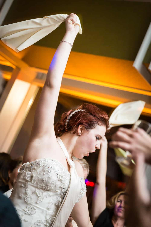 Nicotra's Ballroom wedding photos of bride wearing tie waving napkin in air