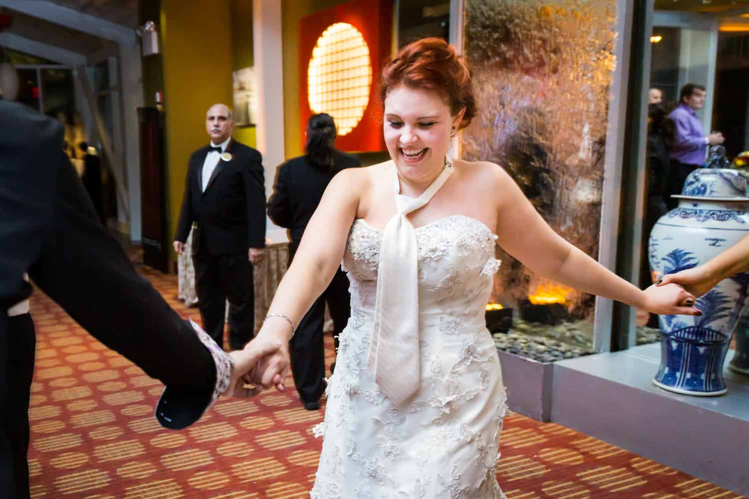 Nicotra's Ballroom wedding photos of bride wearing tie holding hands and dancing
