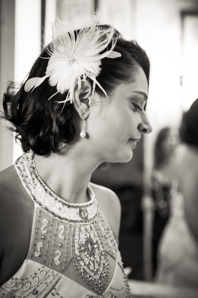 Black and white photo of bride with feathered barrette and beaded 1920s-style dress