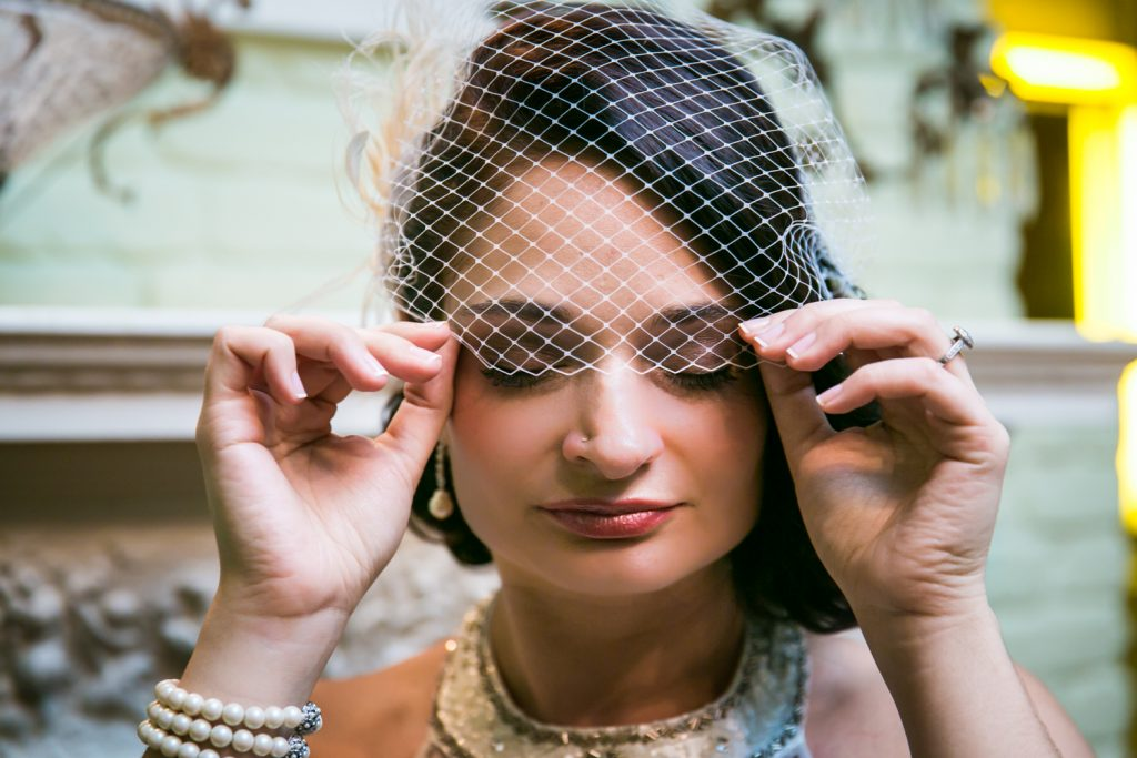 Close up of bride pulling down netting on 1920s-style hat