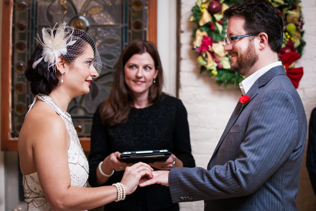 Alger House wedding photos of bride putting ring on groom's finger during ceremony