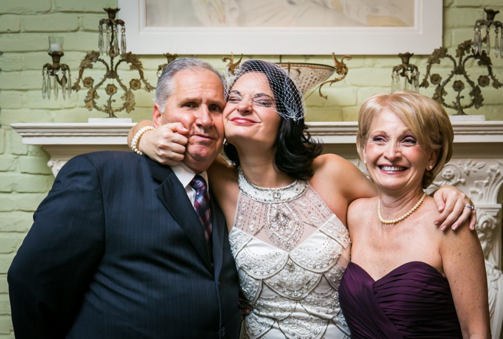 Bride posing with both parents and pinching father's cheeks