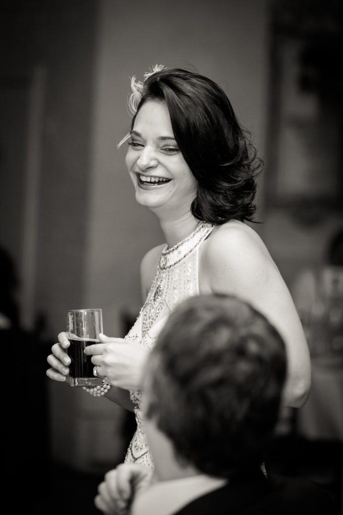Black and white photo of bride holding glass of wine and laughing