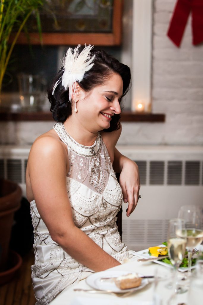 Bride laughing at table while wearing 1920s-style dress and feathered barrette