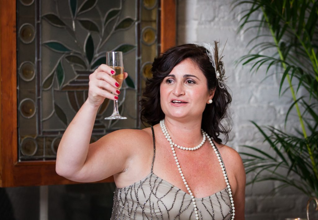Maid of honor wearing 1920s-style dress raising champagne glass