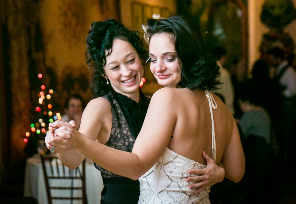 Bride and female guest dancing during 1920s-style wedding