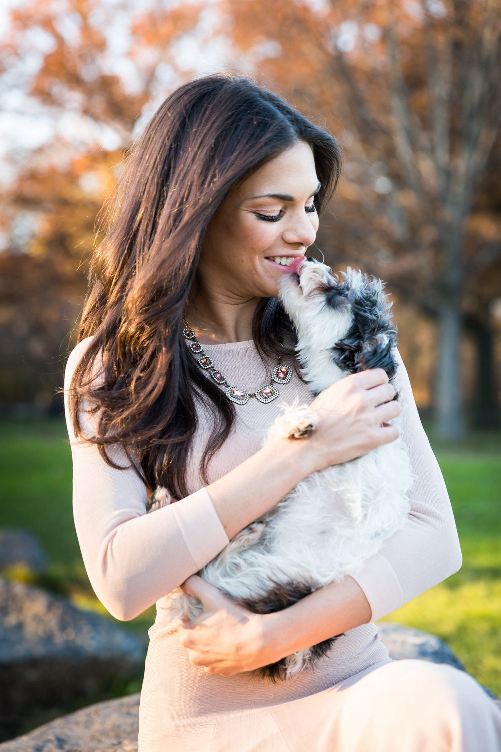 Woman in pink dress holding dog licking her face