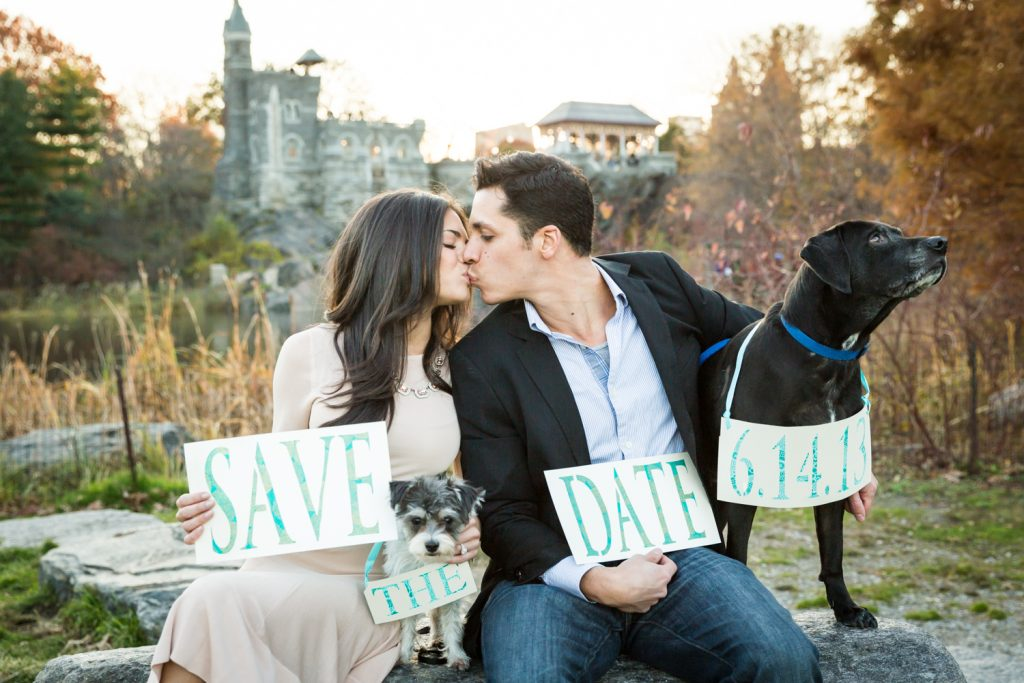 Central Park save-the-date photos of couple kissing and sitting on rock with two dogs holding sign