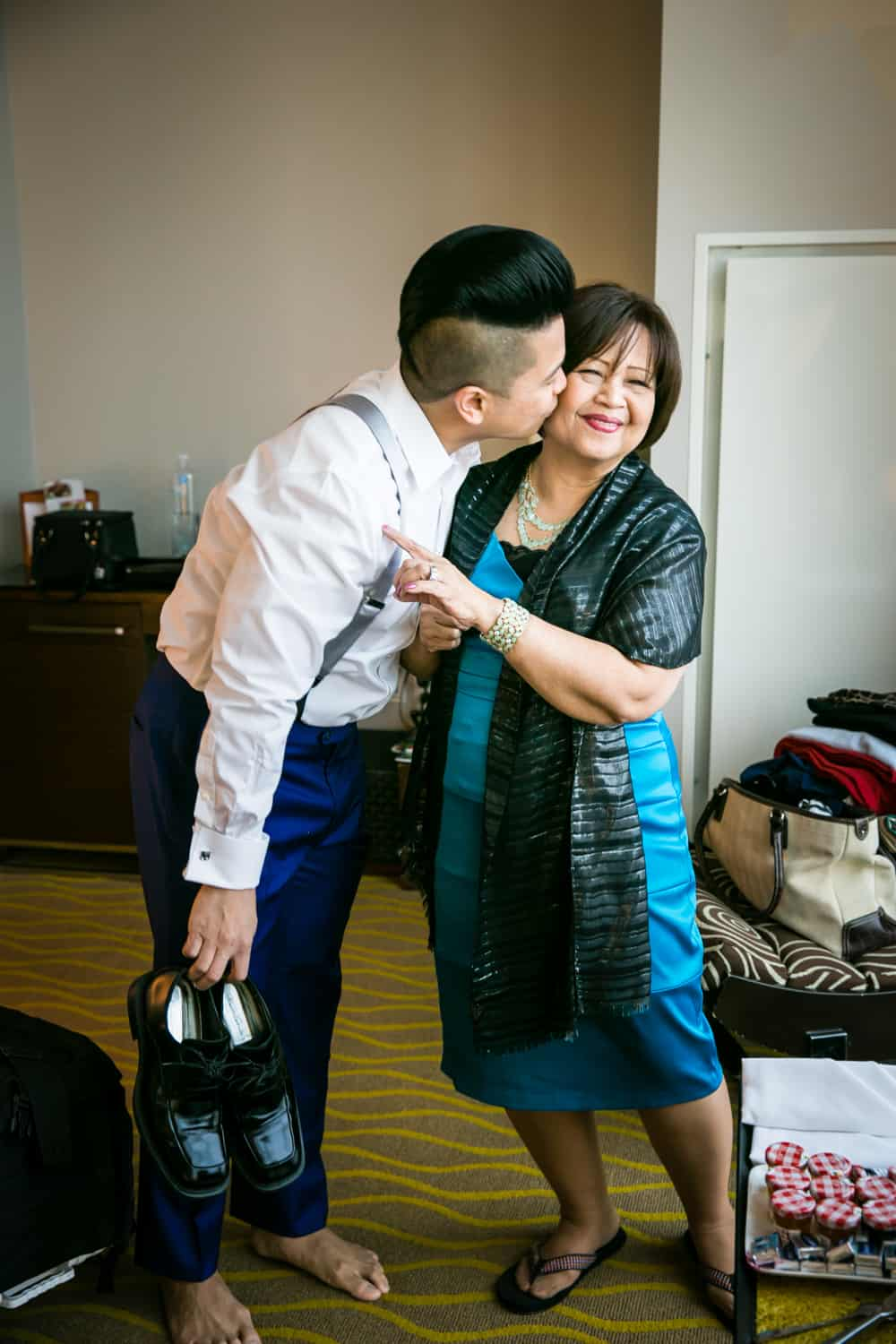 Groom kissing mother on the cheek and holding his shoes