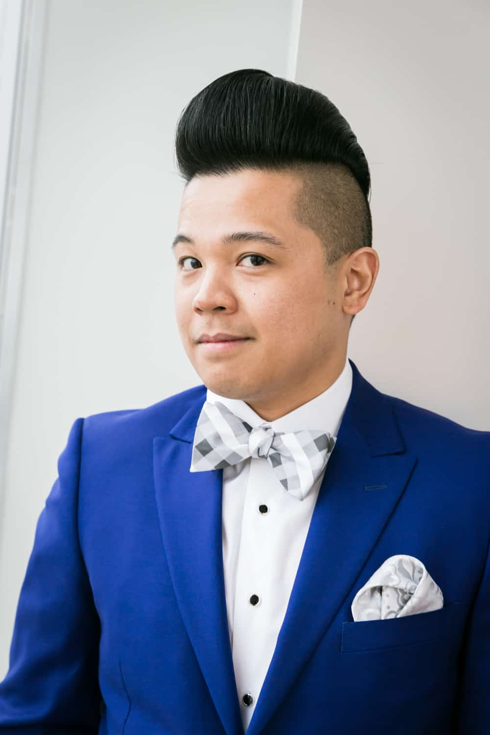 Portrait of groom in blue suit and bow tie