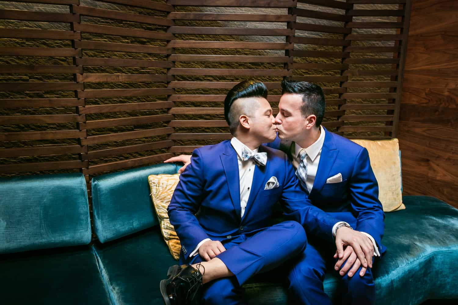 Two grooms in blue suits kissing on a couch