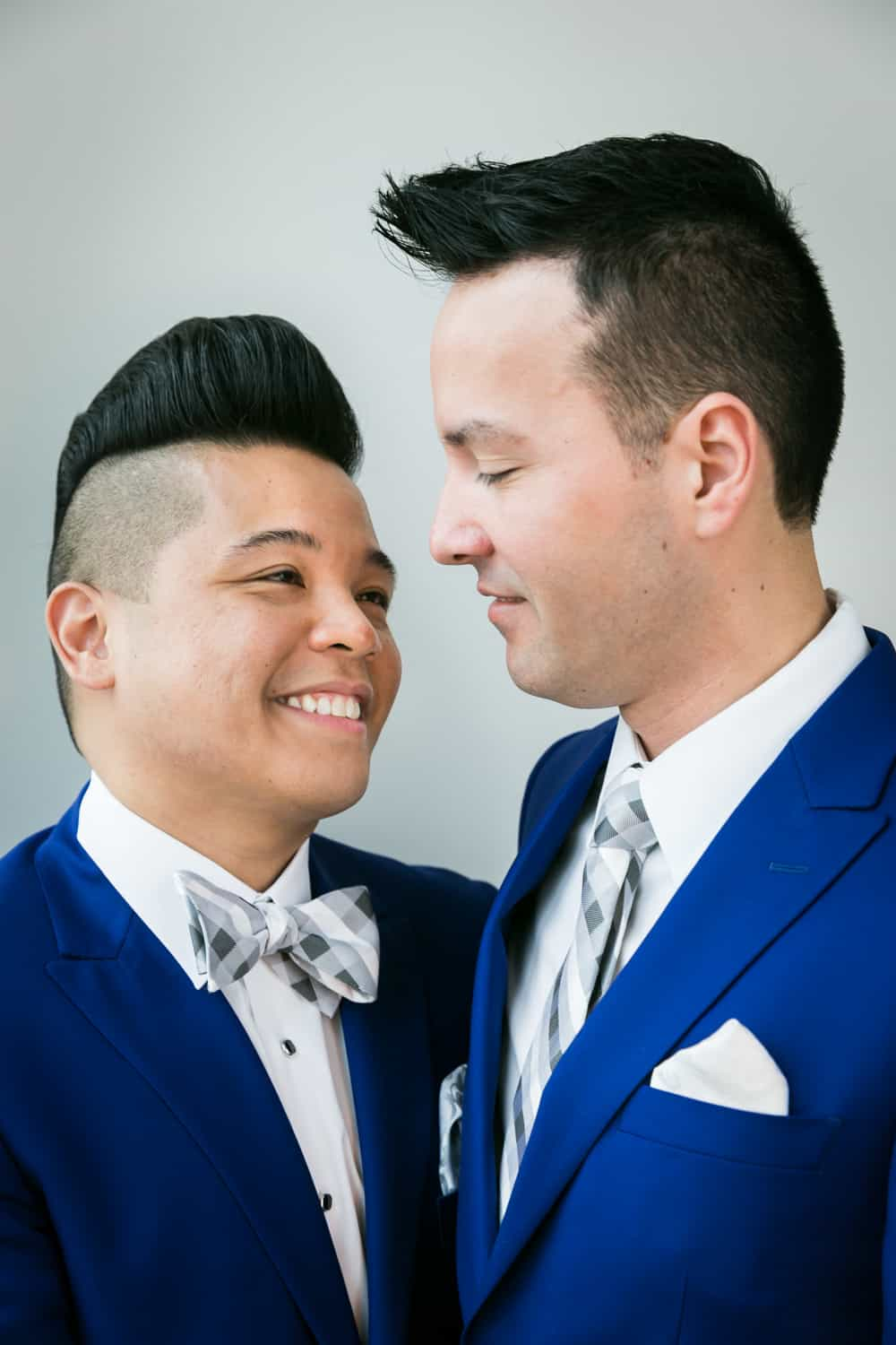 Two grooms in blue suits looking at each other