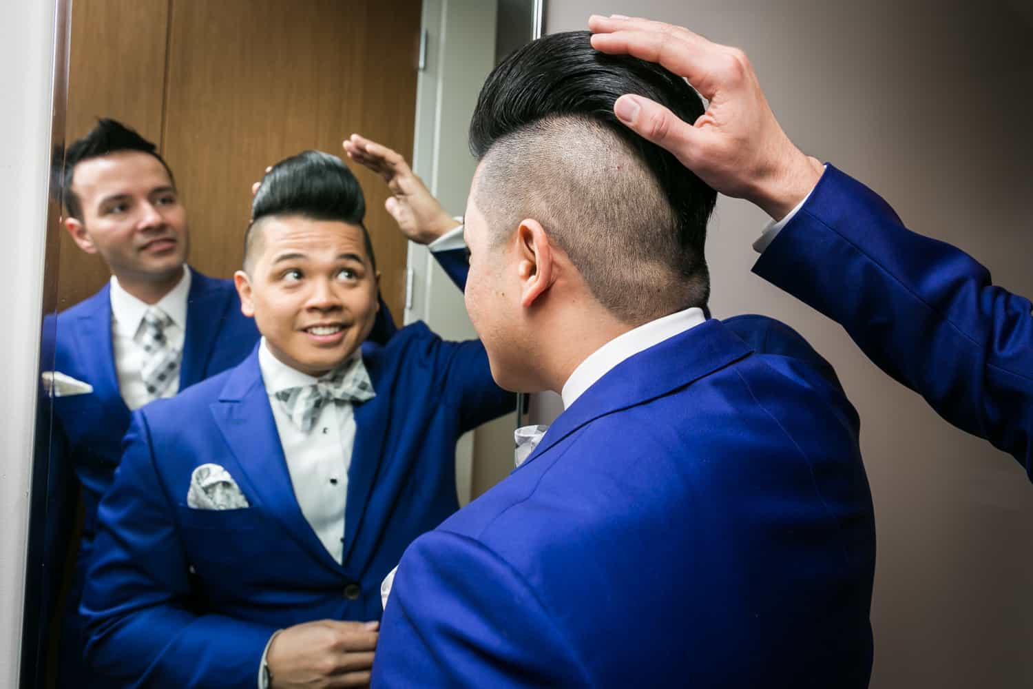Two grooms looking in mirror and one groom touching the other's hair