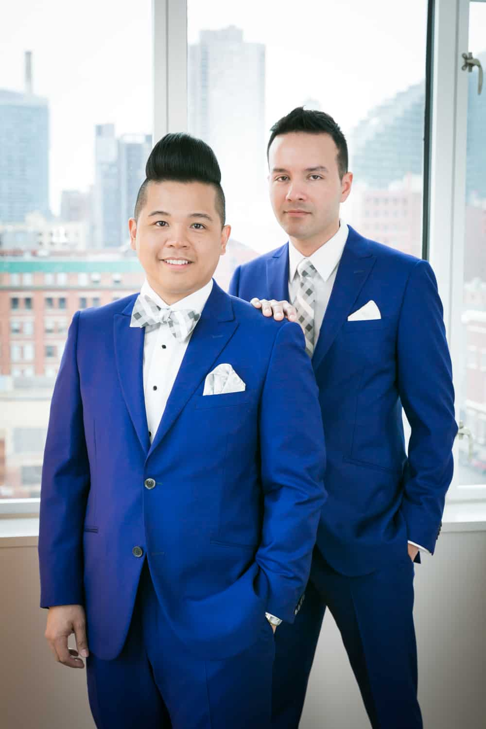 Two grooms in front of window