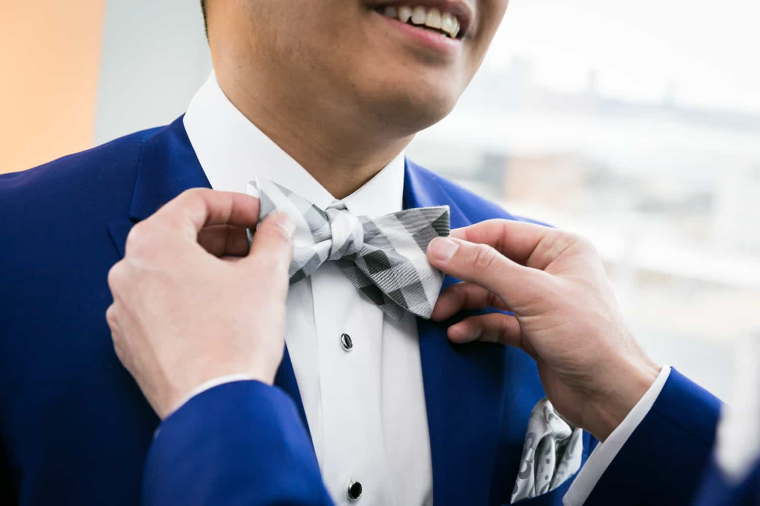 Close up on hands adjusting a groom's bow tie