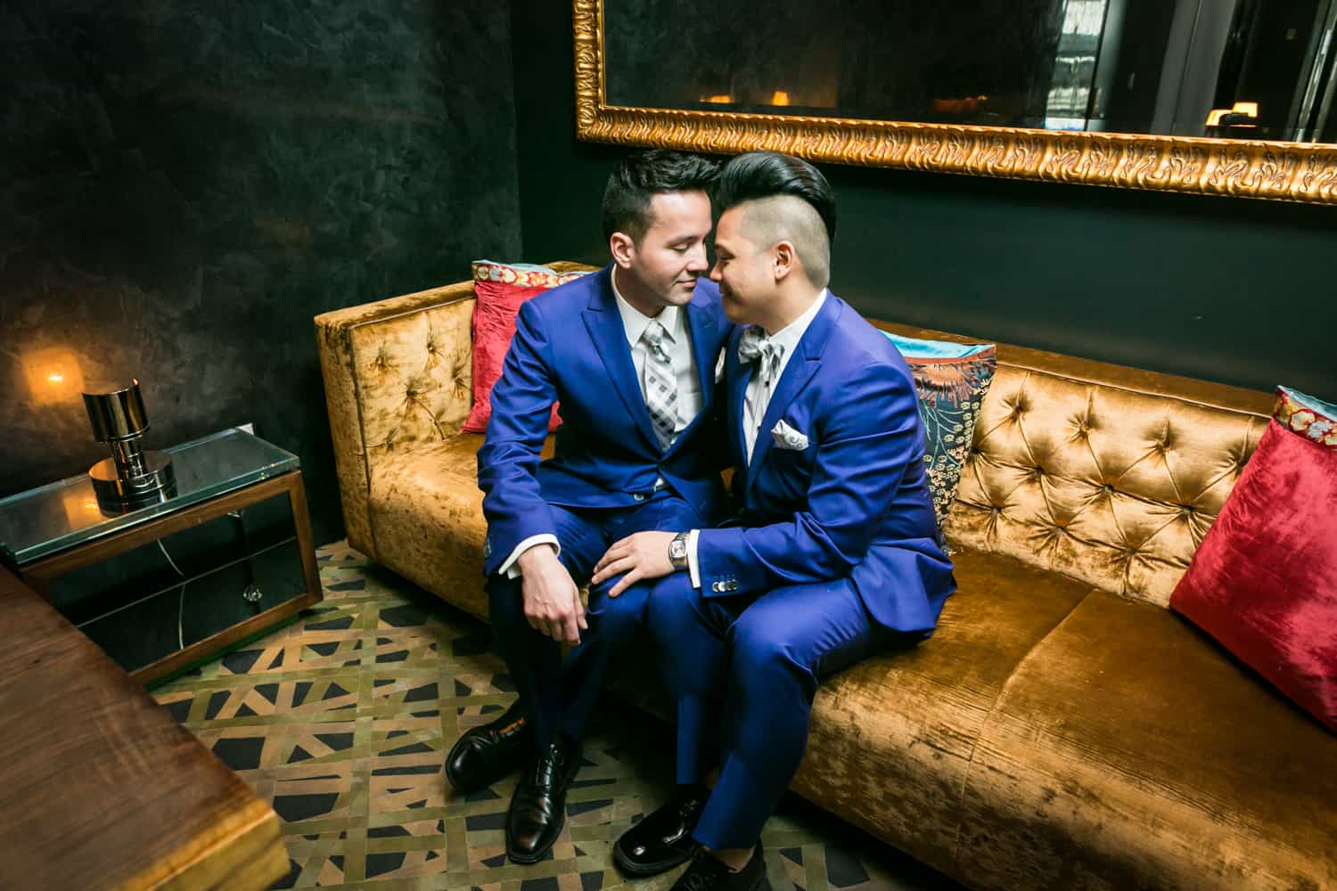 Two grooms cuddling on a couch