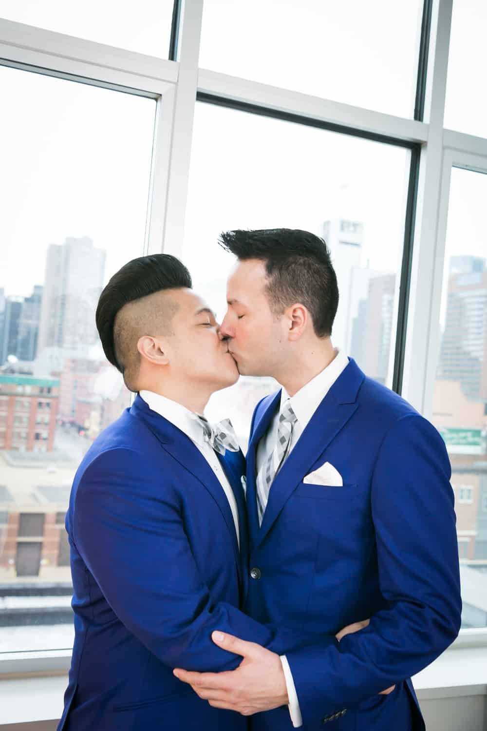 Two grooms kissing in front of window
