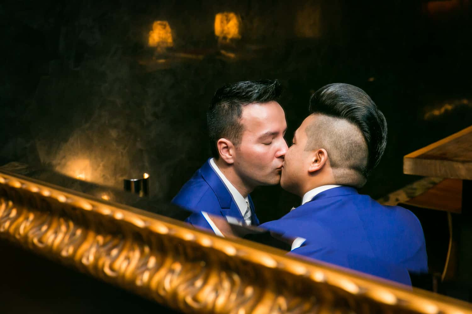 Reflection in mirror of two grooms kissing