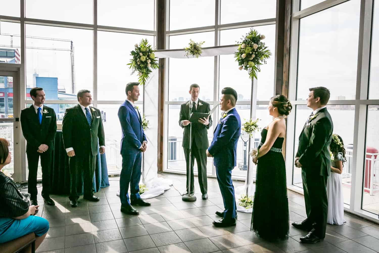 Bridal party standing in front of window during ceremony at a Lighthouse at Chelsea Piers wedding