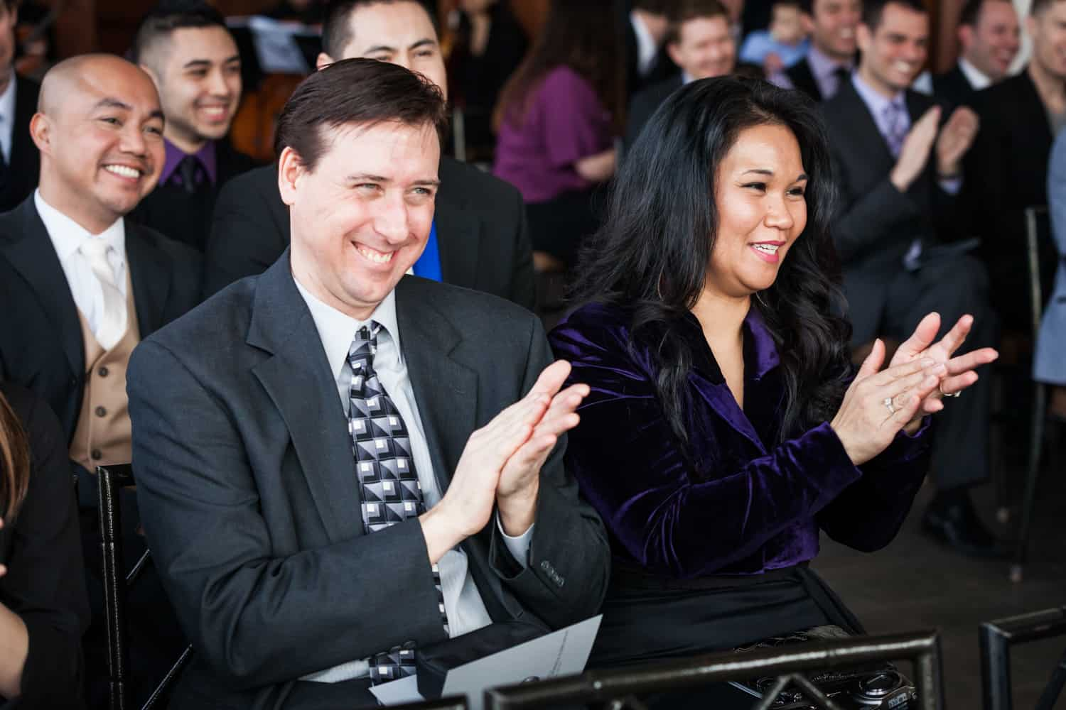 Two guests clapping during ceremony at a Lighthouse at Chelsea Piers wedding