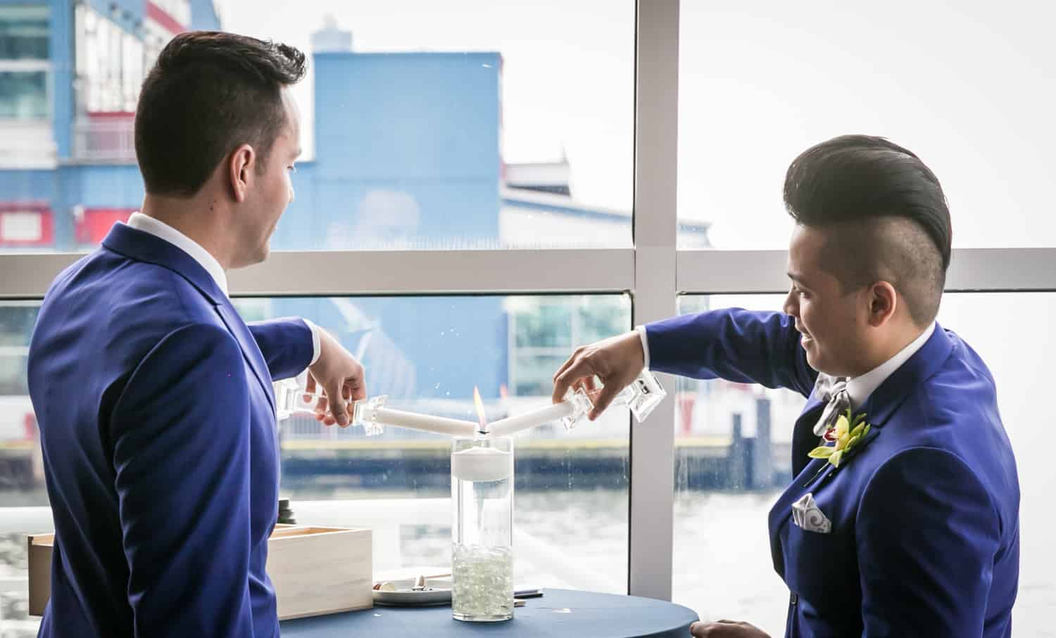 Two grooms lighting unity candle at a Lighthouse at Chelsea Piers wedding