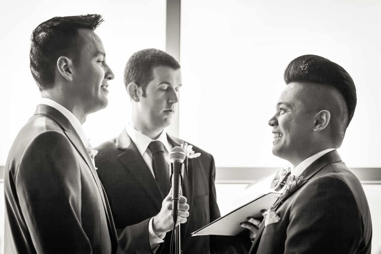 Black and white photo of two grooms exchanging vows