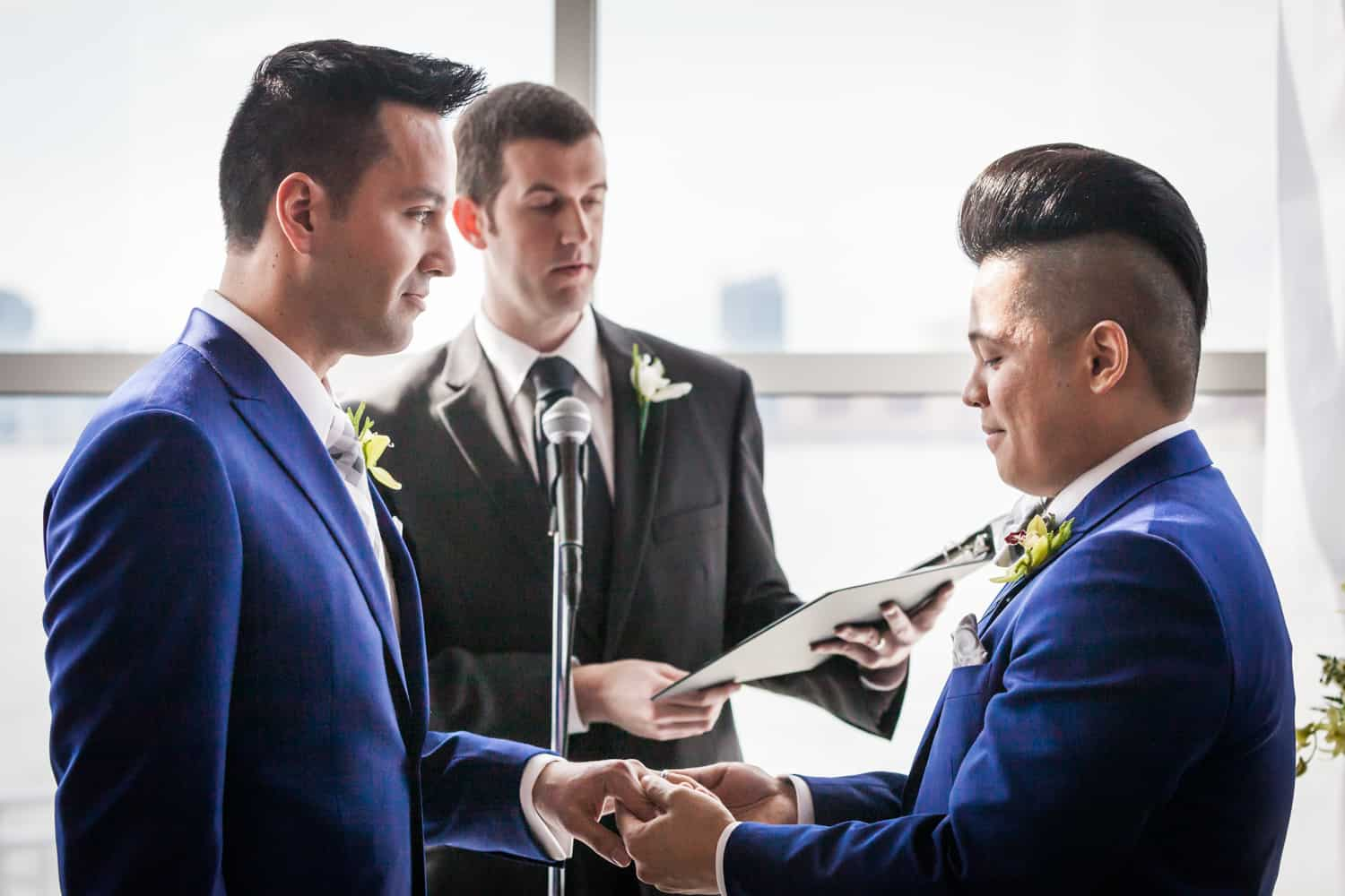 Two grooms exchanging rings at a Lighthouse at Chelsea Piers wedding