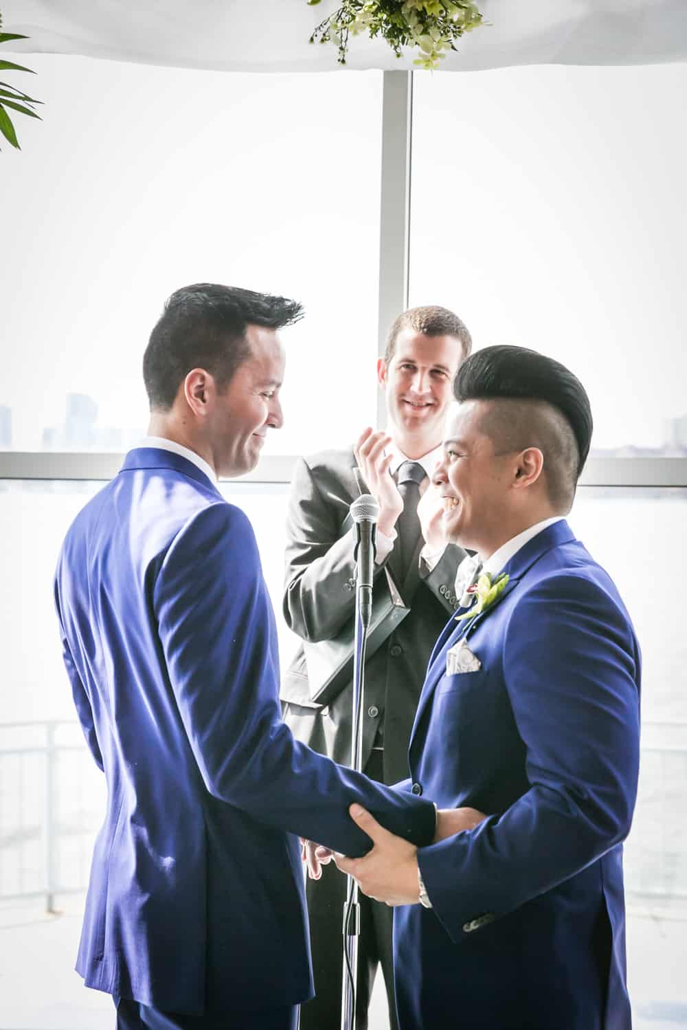Two grooms during ceremony at a Lighthouse at Chelsea Piers wedding