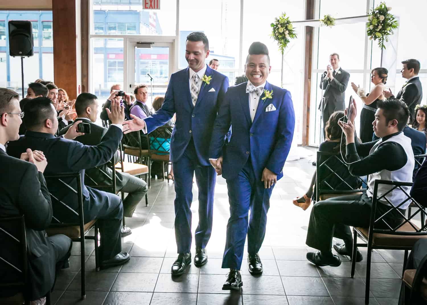 Two grooms walking out of ceremony at a Lighthouse at Chelsea Piers wedding