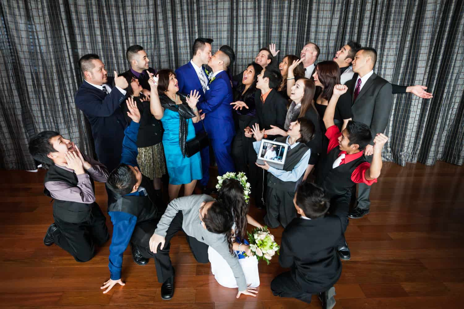 Family cheering around two grooms kissing