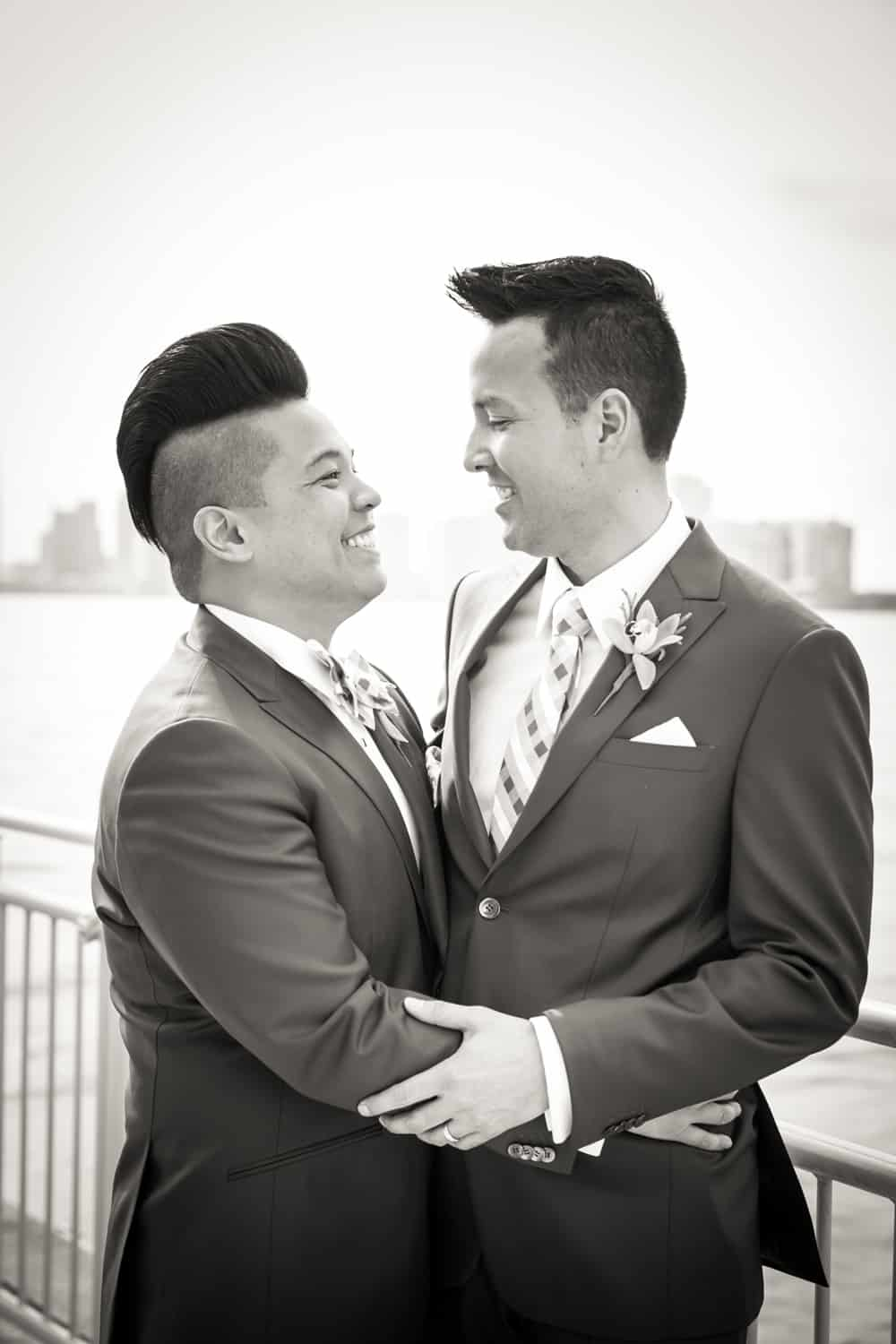 Black and white photo of two grooms beside Hudson River waterfront