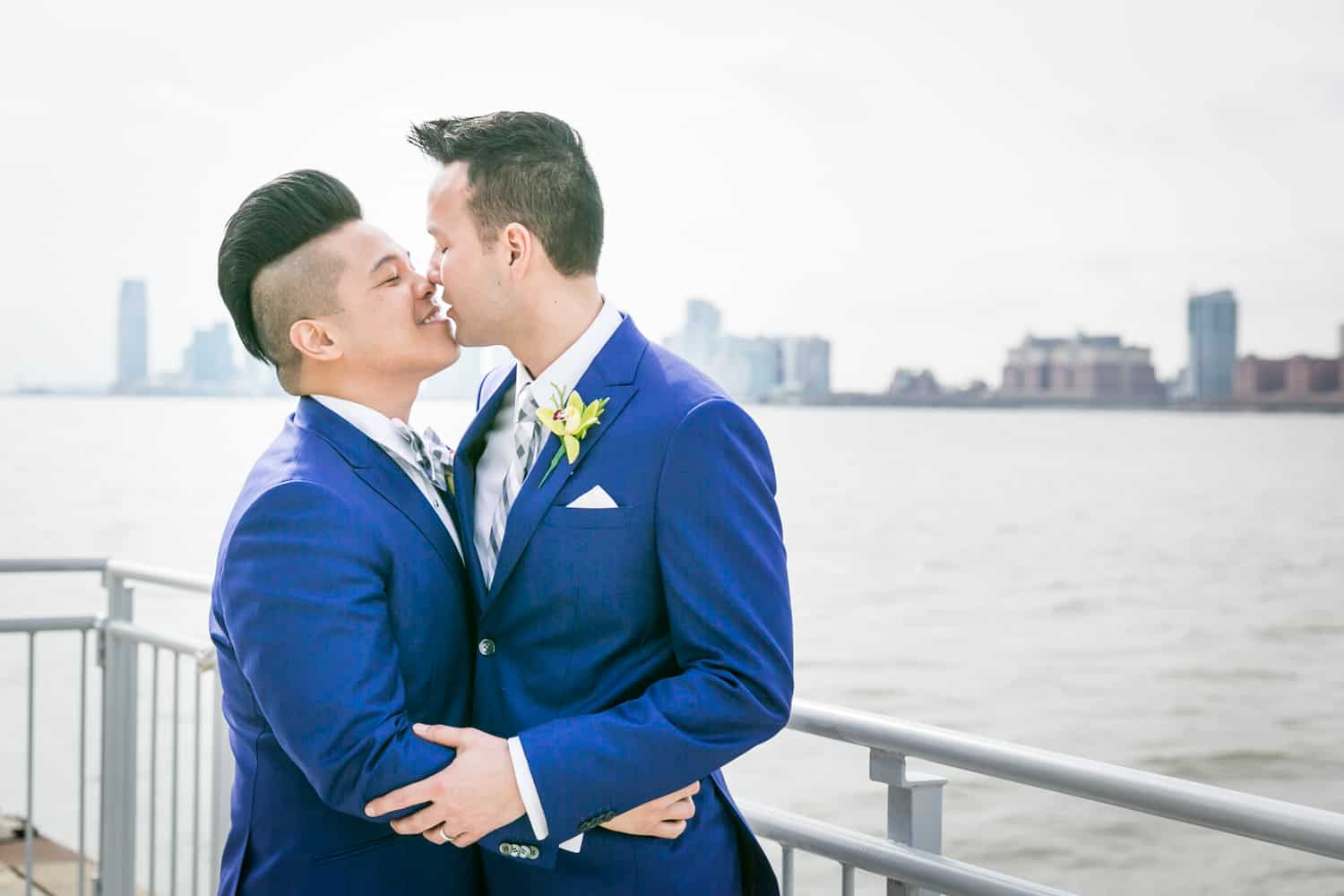 Two grooms kissing beside Hudson River waterfront