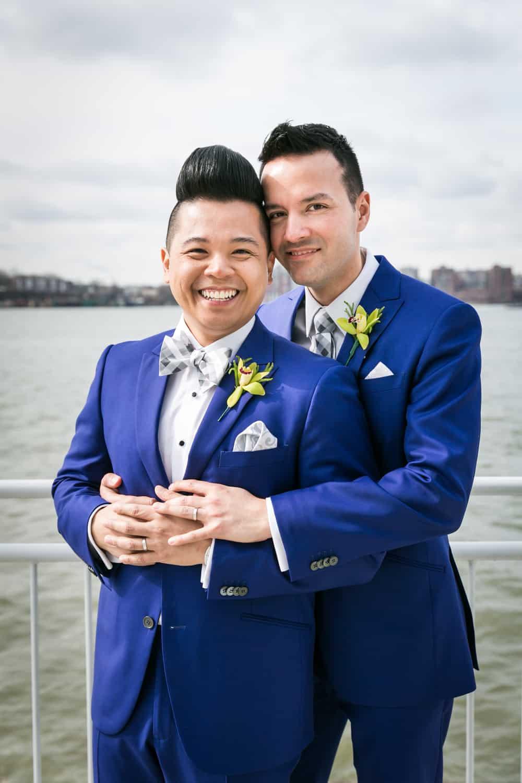 Two grooms hugging beside Hudson River waterfront