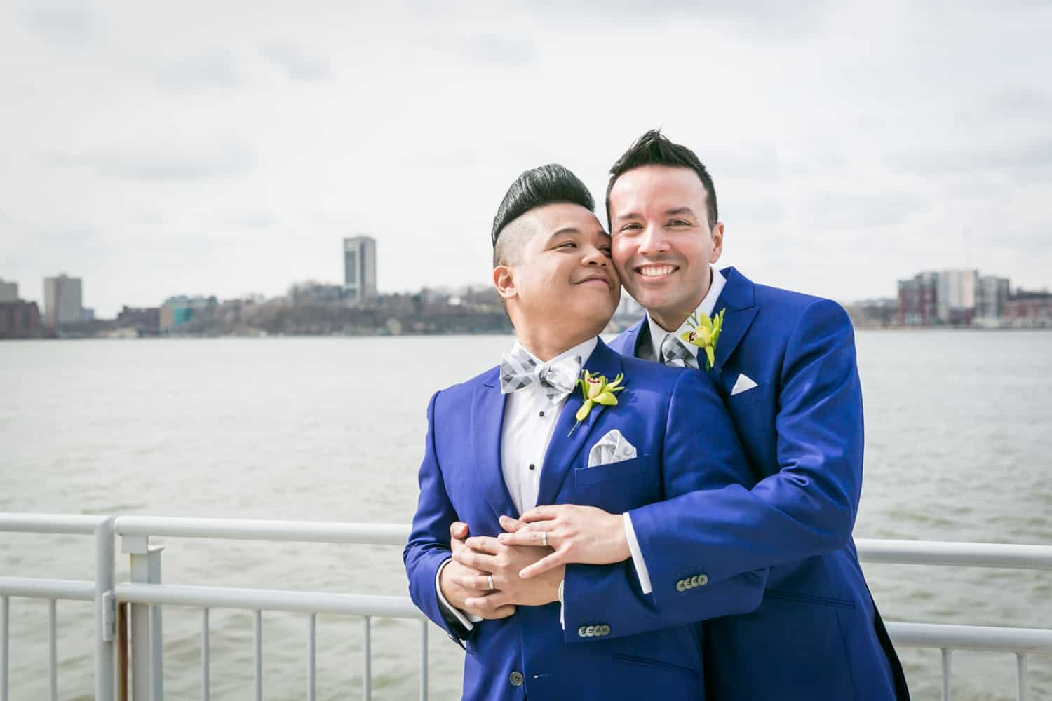 Two grooms hugging by Hudson River waterfront