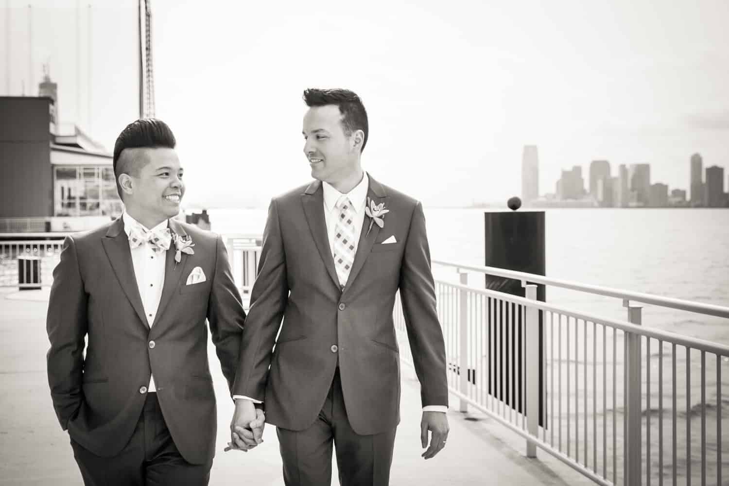 Black and white photo of two grooms walking beside Hudson River waterfront