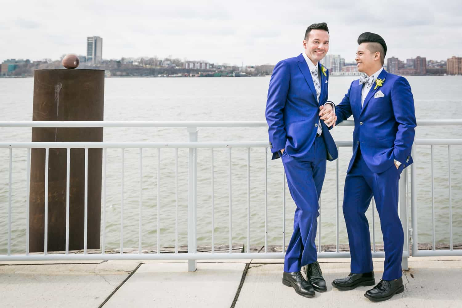 Two grooms leaning on railing by Hudson River waterfront at a Lighthouse at Chelsea Piers wedding
