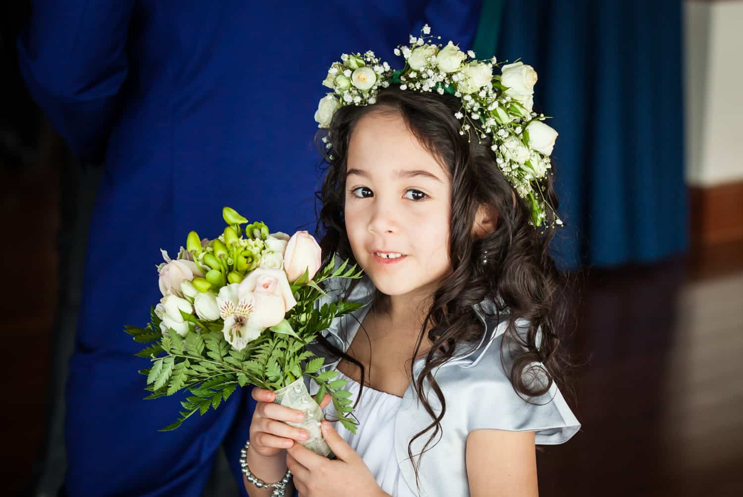 Little flower girl holding bouquet and wearing flower crown