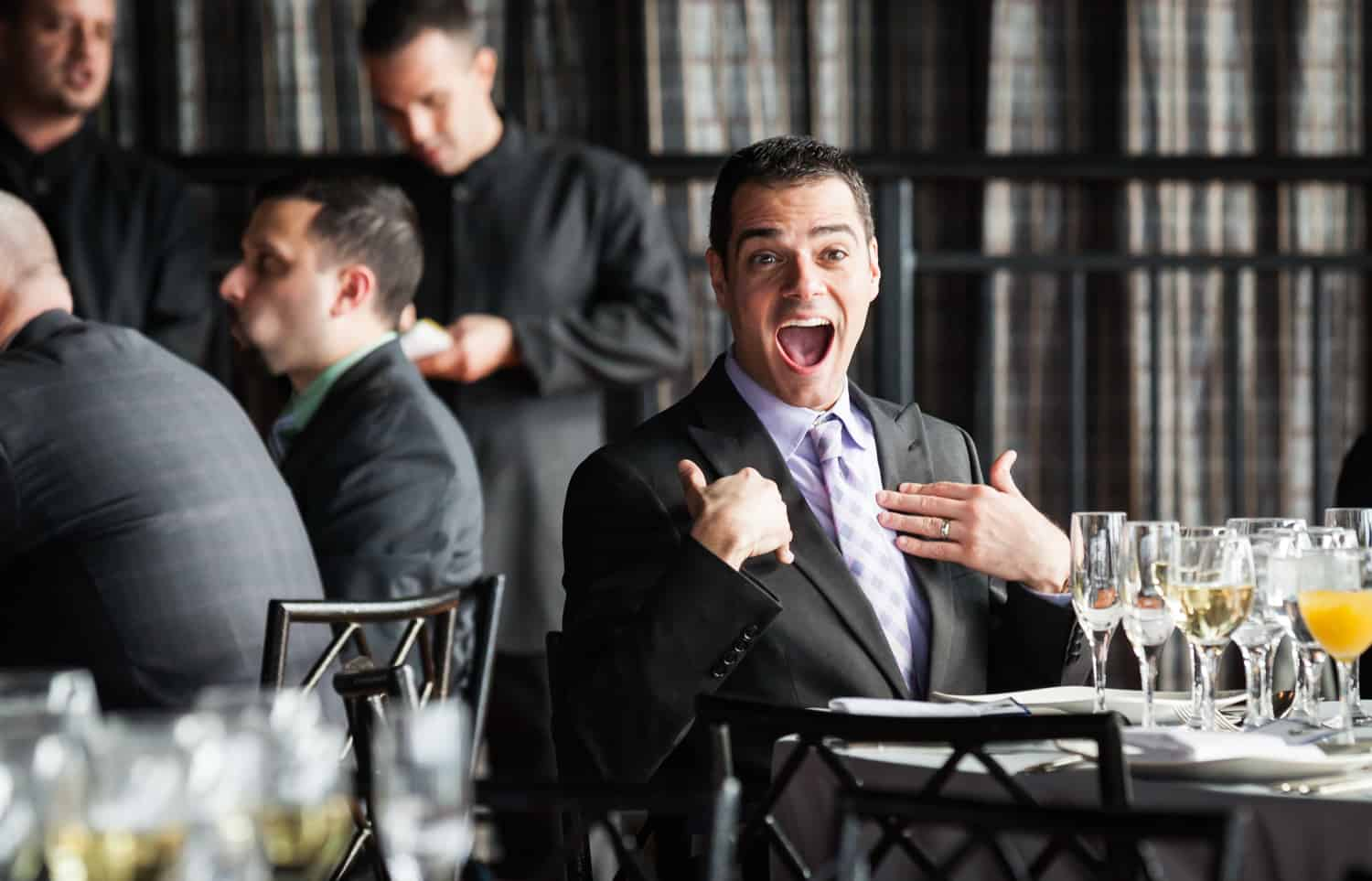 Male guest gesturing to himself at table