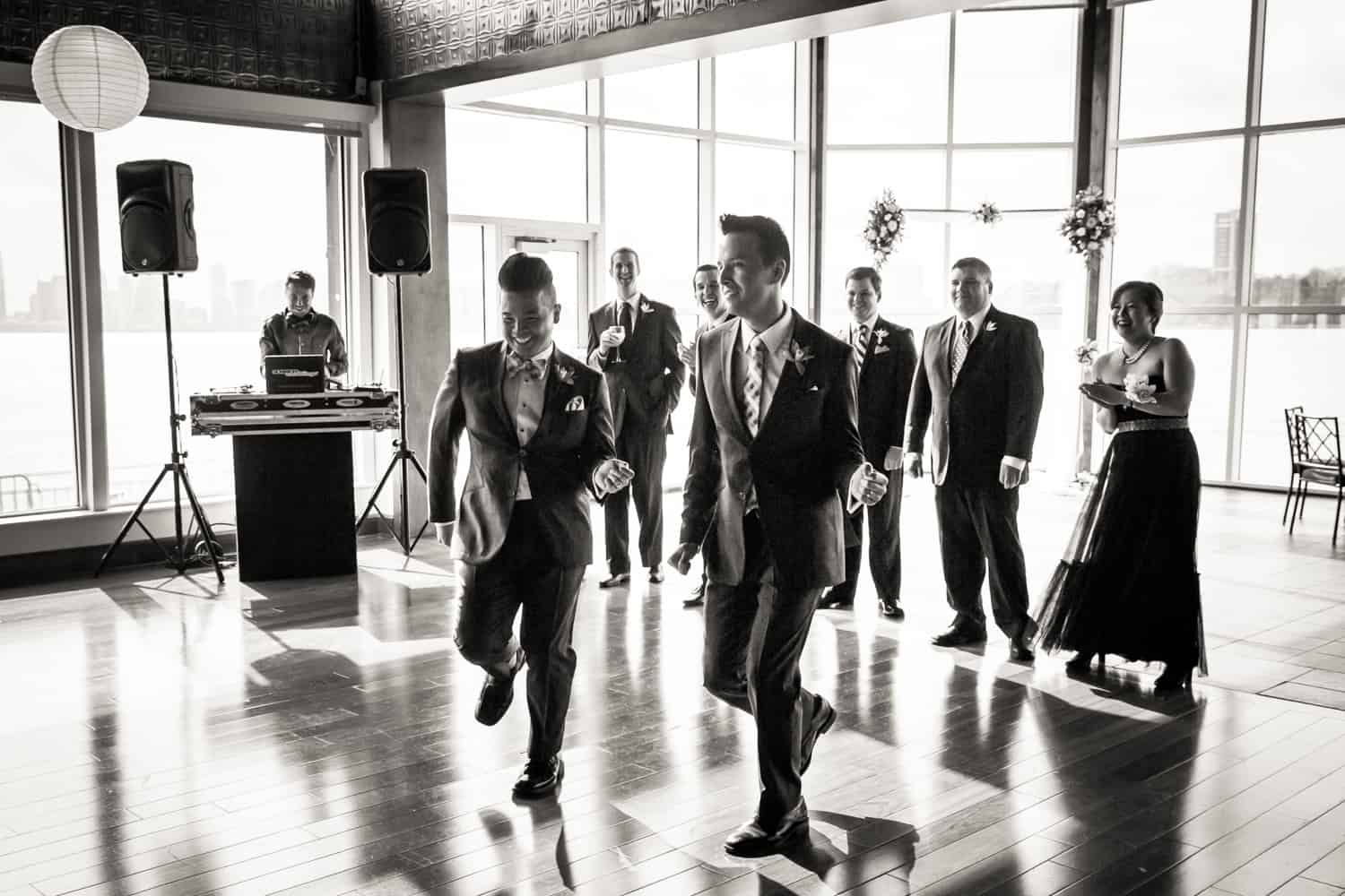 Black and white photo of two grooms dancing in front of bridal party