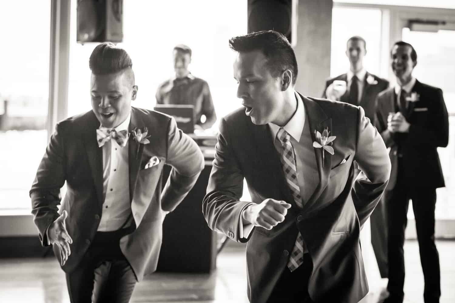 Black and white photo of two grooms dancing in front of guests at a Lighthouse at Chelsea Piers wedding