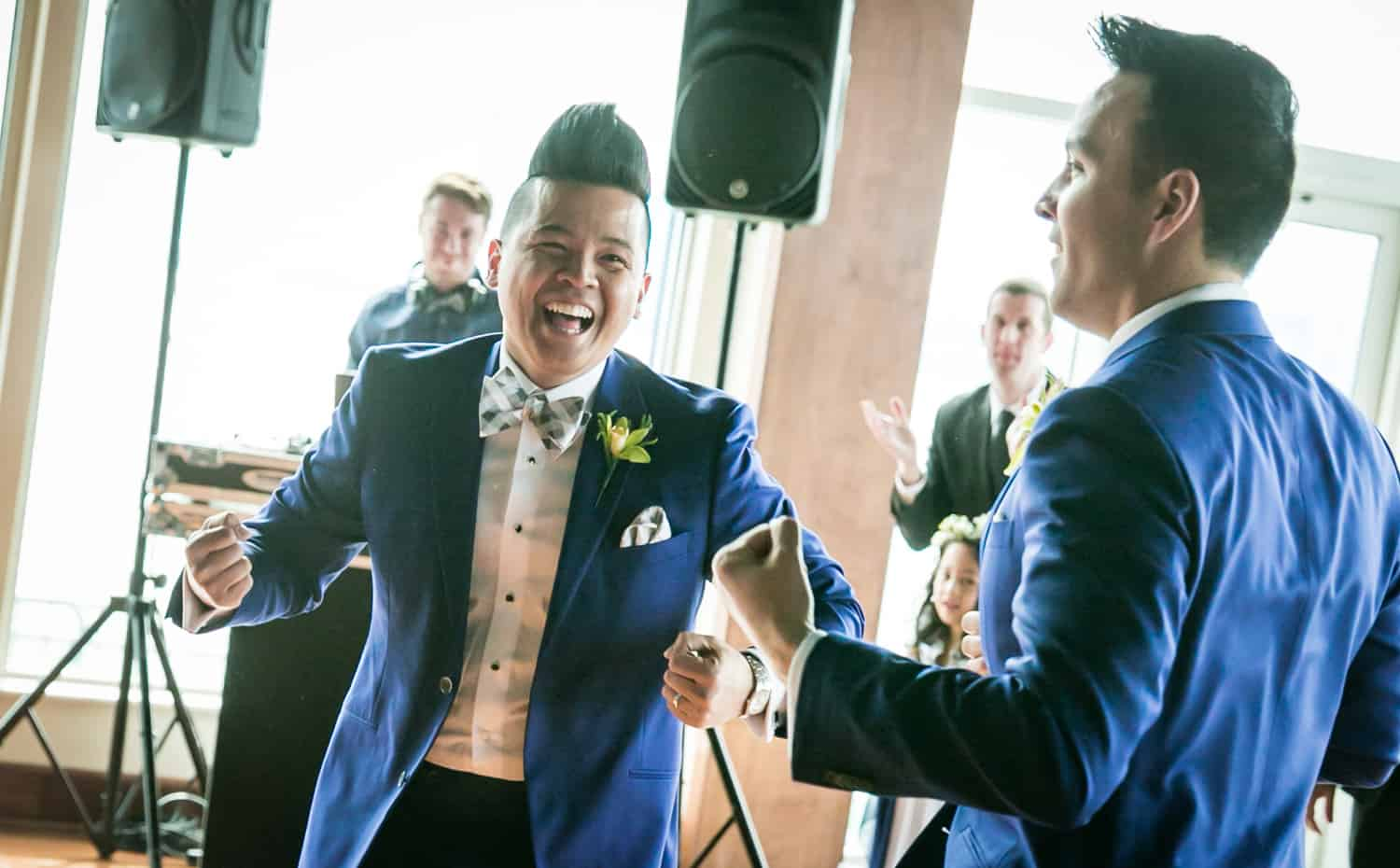 Two grooms dancing in front of guests at a Lighthouse at Chelsea Piers wedding
