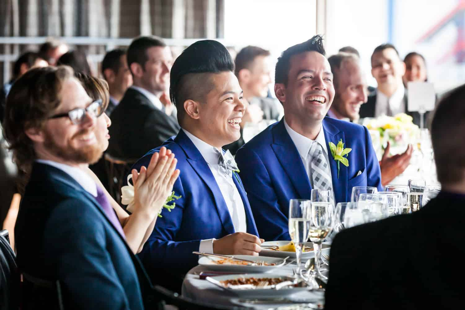 Grooms and guests watching speeches at a Lighthouse at Chelsea Piers wedding