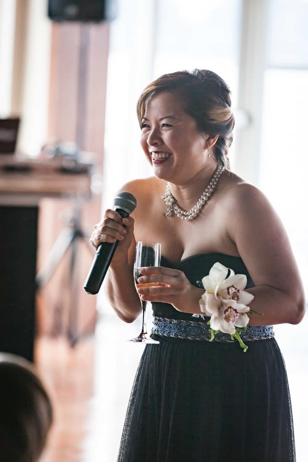 Maid of honor holding champagne glass and making speech into microphone