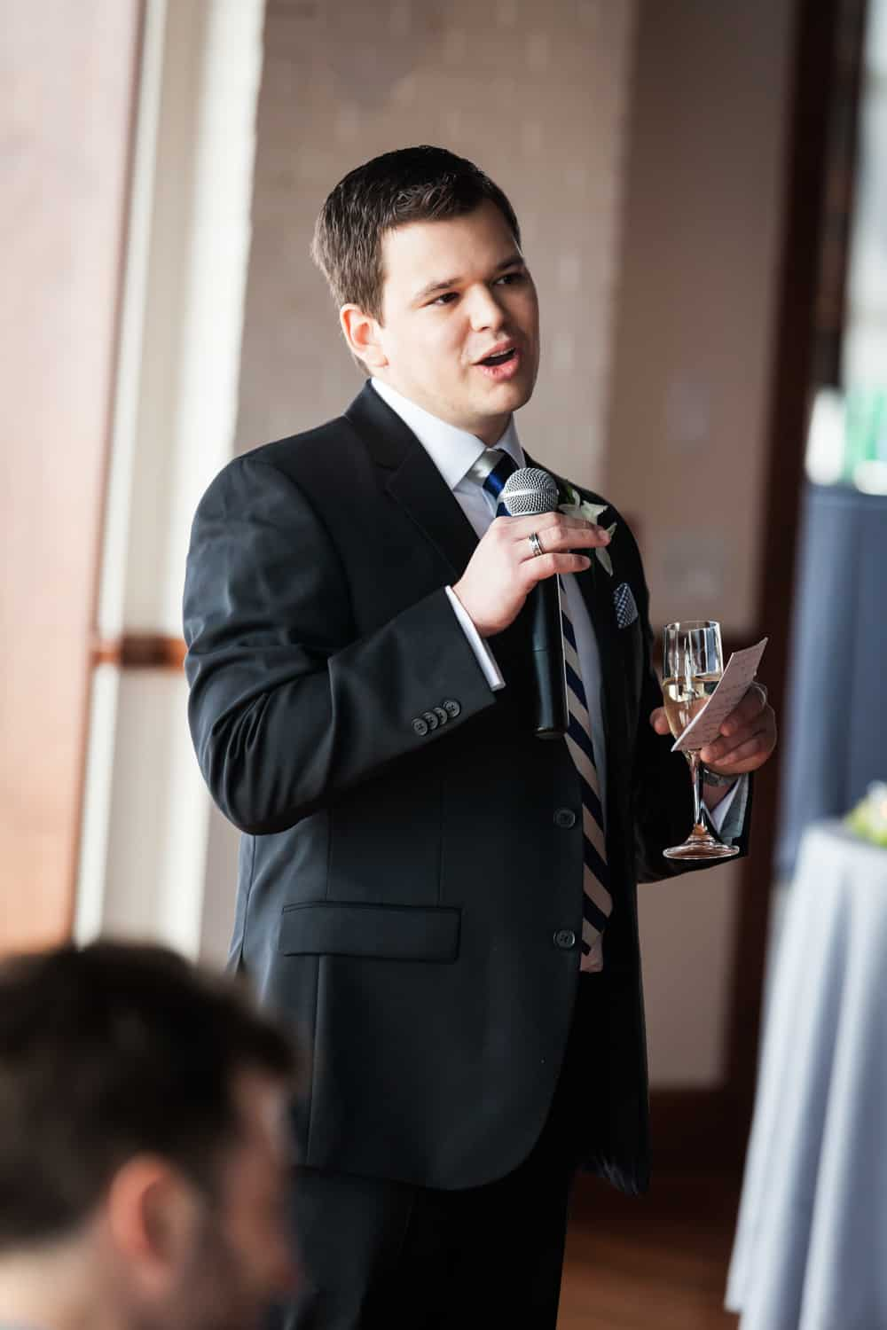Best man holding champagne glass and making speech into microphone
