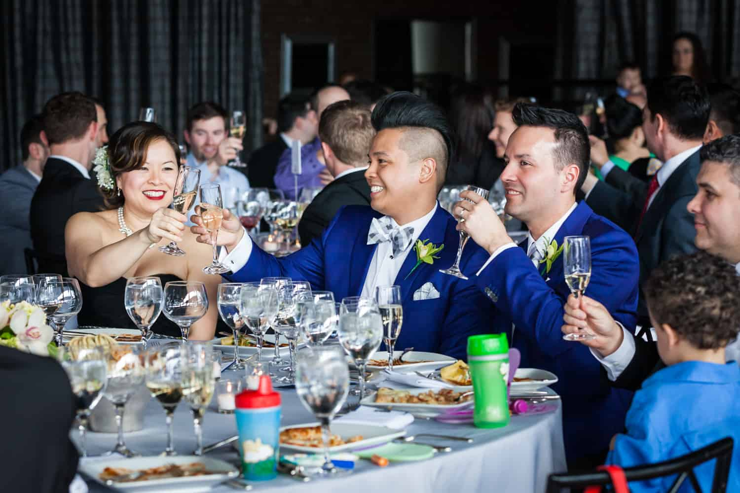 Two grooms toasting champagne glasses with guests at a Lighthouse at Chelsea Piers wedding