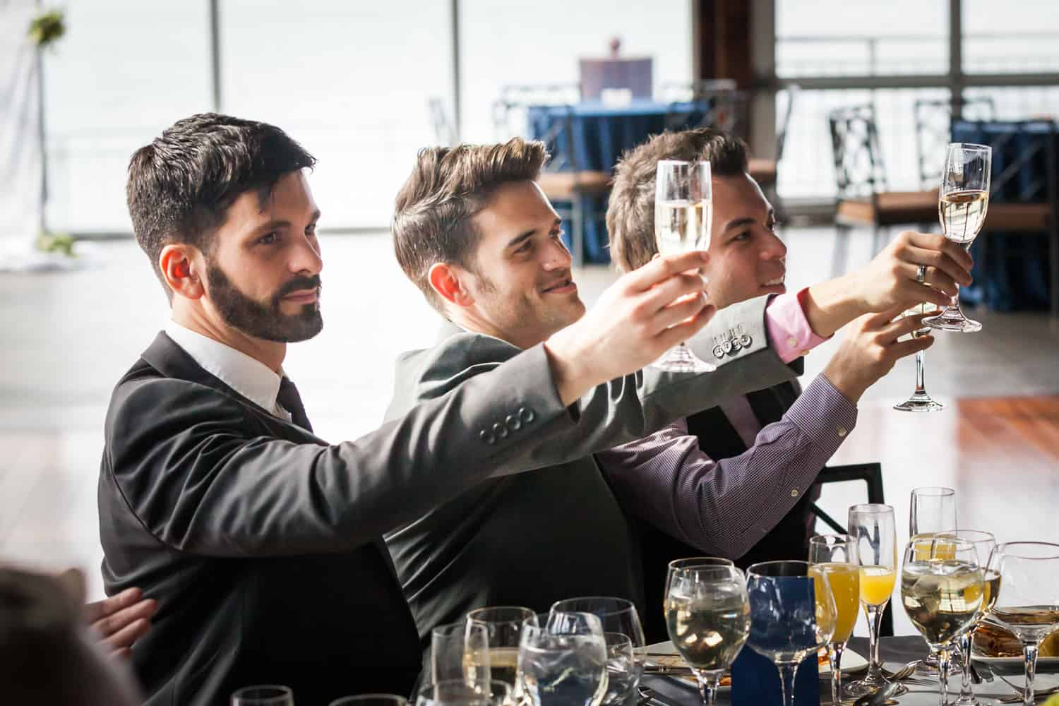 Three male guests holding up champagne glasses at a Lighthouse at Chelsea Piers wedding